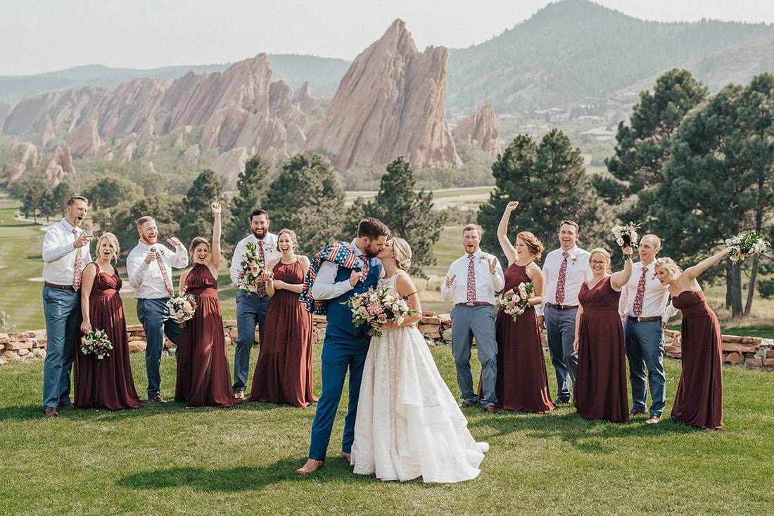bride and groom kissing with bridal party celebrating